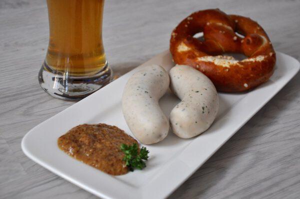Paar Weißswürst mit süßem Senf und Bretze mit Weizen im Hintergund | Metzgerei Herpich Hof
